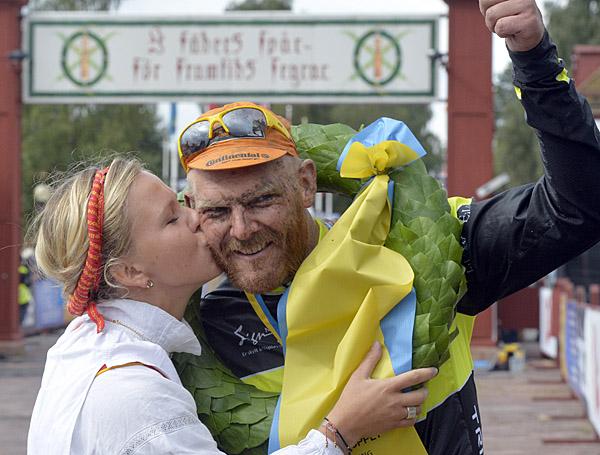 Johan Landström, Motala AIF, får segerkyssen efter CykelVasan 2014 av kranskullan Lisa Englund. Fotograf/Källa: Vasaloppet/Nisse Schmidt -